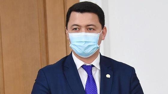 Камалжан Надыров в маске стоит в кабинете