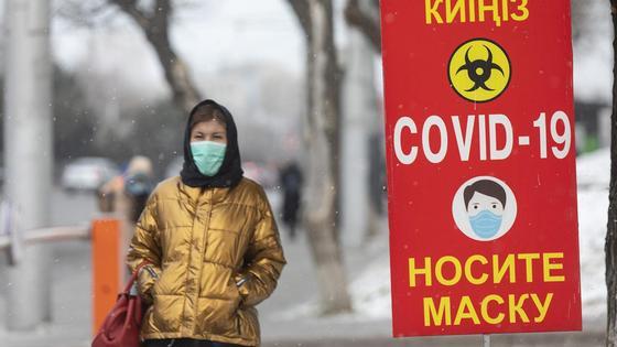 Девушка в куртке и маске идет по улице