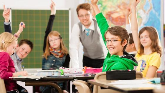 Дети за партой поднимают руку для ответа