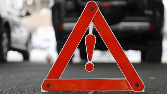 Складной аварийный знак стоит на асфальте