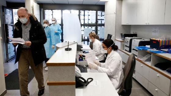 мужчина с бумагами стоит у стойки регистрации в поликлинике