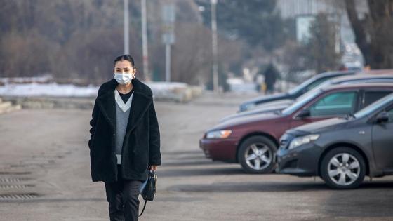 Женщина в черной куртке с сумкой в руках идет по городу