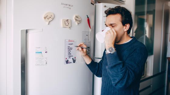 Мужчина стоит рядом с холодильником
