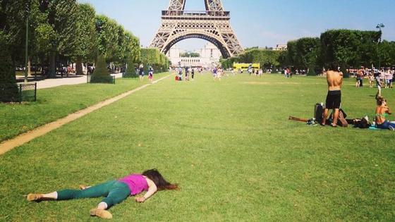 Художница Стефани Ли Роуз лежит на газоне перед Эйфелевой башней