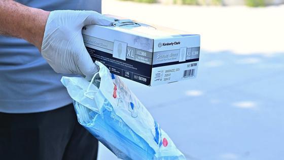 Мужчина держит в руках упаковку с медицинскими масками