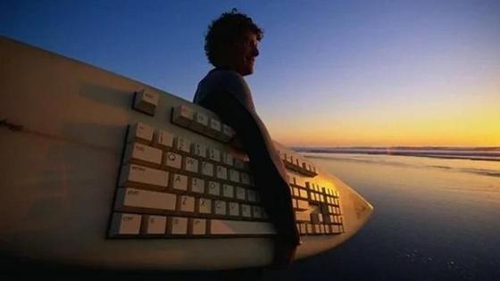 мужчина держит доску для серфинга с клавиатурой на ней