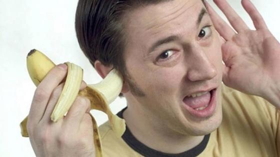 мужчина держит банан в ухе