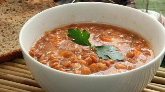 Суп из красной чечевицы в глубокой тарелке с листиком петрушки